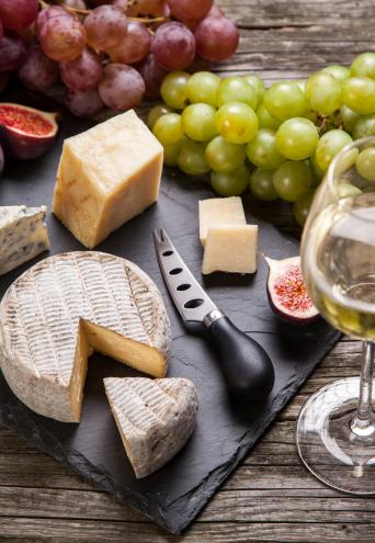 A top down photograph of grapes, various cheeses and cheese board